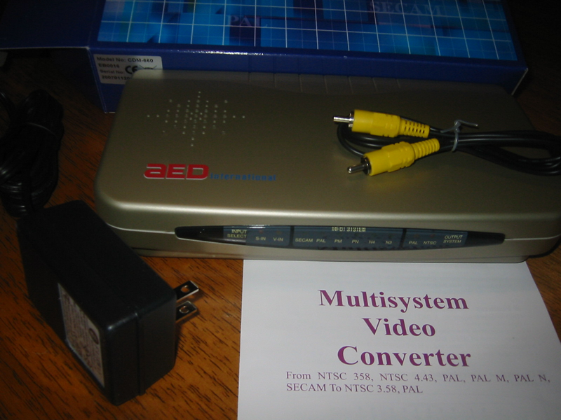 Picture of an AED Multisystem Video Converter, which can accept input signals encoded using any of the three major analog video encoding standards (NTSC, SECAM, and PAL), and convert them to output signals encoded using either NTSC or PAL. It accepts North American 110V/60Hz current and even has a North American plug.