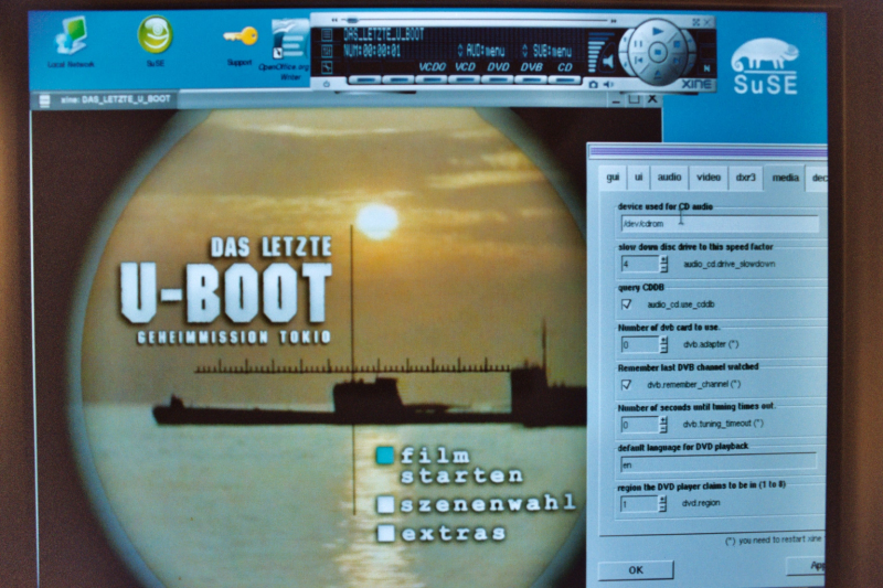 "Screenshot of a Linux desktop showing the DVD playing software ""xine"" package displaying the title menu of a region code 2 DVD of the film ""Das letzte Boot"" and the configuration dialog box where the user tells the software what region code the software should pass to the DVD drive."